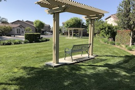 A green metal park bench under a yellow trellis overlooks a green lawn, near where Equity Group provides Kings County property management