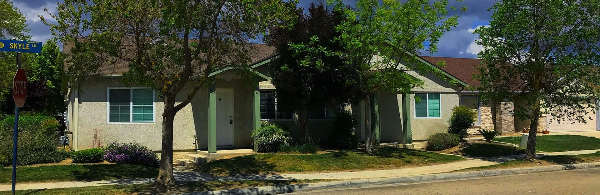 A beige house with a touch of green color and trees in front; The Equity Group Values Tenants